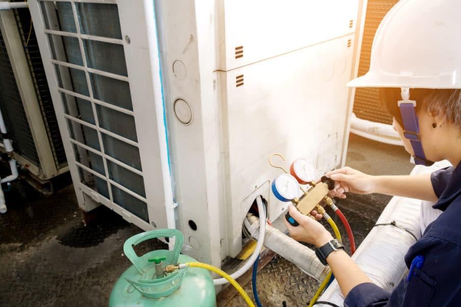 Tech checking AC compressor